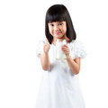 Happy little asian girl holding a cup of milk isolated over white Stock Image
