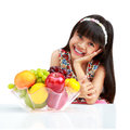 Happy little asian girl sitting on the table with plate of fruit isolated white Stock Images