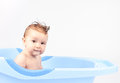Happy little babe is bathed in blue basin Royalty Free Stock Photo
