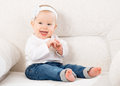 Happy little baby girl laughing and sitting on a sofa in jeans white blue Stock Photos