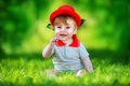 Happy little baby in red hat having fun in the park on solar gla Royalty Free Stock Photo