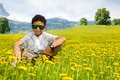 Happy little black sitting boy in sunglasses the dandelion field with mountains on background Stock Photos