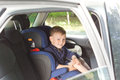Happy little boy in a child seat view through the open window of car of strapped into Stock Photo