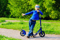 Happy little boy enjoy riding scooter in summer kids sport Stock Images