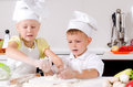 Happy little boy and girl cooking in the kitchen wearing a white chefs uniform hat standing at counter making a batch of Royalty Free Stock Photo