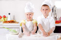 Happy little boy and girl cooking in the kitchen wearing a white chefs uniform hat standing at counter making a batch of Royalty Free Stock Photos