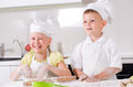 Happy little boy and girl cooking in the kitchen wearing a white chefs uniform hat standing at counter making a batch of Stock Photography