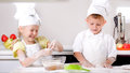 Happy little boy and girl cooking in the kitchen wearing a white chefs uniform hat standing at counter making a batch of Stock Image