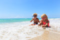 Happy little boy and girl play with water on beach Royalty Free Stock Photo