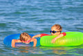 Happy little boy and girl swim at summer beach Royalty Free Stock Photo