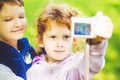 Happy little boy and girl taking self photo in the autumn park Royalty Free Stock Photo