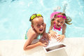 Happy little boy and girl using laptop in pool Royalty Free Stock Photo