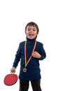 Happy little boy with gold medal at his neck and table tennis racket in hand Royalty Free Stock Photo