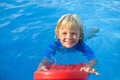 Happy little boy has fun with floating board in swimming pool Royalty Free Stock Photo