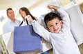 Happy little boy holding shopping bags his family Royalty Free Stock Photography