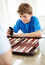 Happy little boy playing backgammon game Royalty Free Stock Images