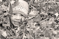 Happy little boy playing in the leaves buried a pile of with just his face sticking out he is smiling and and wearing a crocheted Royalty Free Stock Photos