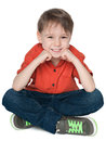 Happy little boy in the red shirt a is sitting on white background Royalty Free Stock Photo