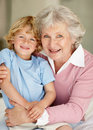 Happy little boy sitting on his grandmothers lap Royalty Free Stock Photo