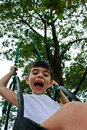 Happy Little Boy Smiling on Swing Stock Photo
