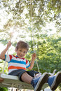 Happy little boy on a swing in the park Royalty Free Stock Photo