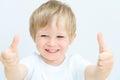 Šťastný malý chlapec palec nahoru na bílém
