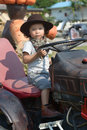 Happy little boy of two years having fun on tractor in summer Stock Image