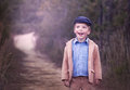 Happy little boy wearing a hat standing on a path Royalty Free Stock Photo
