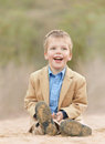 Happy little boy wearing a yellow jacket sittingon Royalty Free Stock Photo