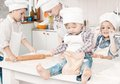 Happy little chefs preparing dough in the kitchen with their hats and aprons Stock Image