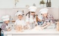 Happy little chefs preparing dough in the kitchen with their hats and aprons Royalty Free Stock Image