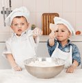 Happy little chefs preparing dough in the kitchen with their hats and aprons Royalty Free Stock Photography
