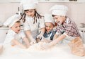 Happy little chefs preparing dough in the kitchen with their hats and aprons Stock Photo