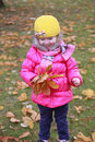 Happy little child, baby girl laughing and playing in the autumn on the nature walk outdoors with yellow hat Royalty Free Stock Photo