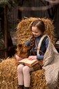 Happy little child girl reads old book with dog on hay Royalty Free Stock Photo