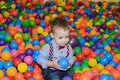 Happy little child playing at colorful plastic balls playground