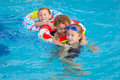 Happy little children playing in the swimming pool at day time Stock Image