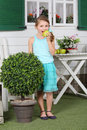 Happy little cute girl in skirt eats apple near white table and cottage Royalty Free Stock Photography