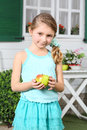 Happy little cute girl in skirt holds apple near white table and cottage with shutters Stock Photo