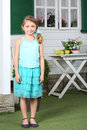Happy little cute girl in skirt stands near white table with apples and cottage Stock Photos