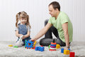 Happy little daughter and her father play toys on soft carpet at home Stock Photo