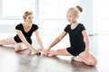 Happy little girl ballerina sitting and stretching legs with teacher Royalty Free Stock Photo