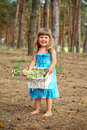 Happy little girl with a basket of flowers in the forest Stock Photos