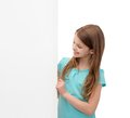 Happy little girl with blank white board people advertisement and sale concept Stock Photo