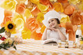Happy little girl with book chef prepares breakfast, smiling and posing for the camera Royalty Free Stock Photo