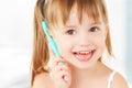 Happy little girl brushing her teeth
