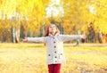 Happy little girl child enjoys warm sunny autumn day looks up walks in park