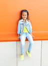 Happy little girl child wearing a sunglasses and jeans clothes Royalty Free Stock Photo