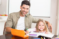 Happy little girl colouring at the table with her father home in kitchen Stock Photography