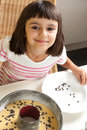 Happy little girl cooking a chocolate chip cake and cute pouring chips to Royalty Free Stock Photo